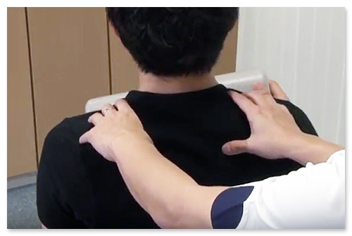 後方変異している肋骨を押しながら、患者さんに左右に動いてもらいます